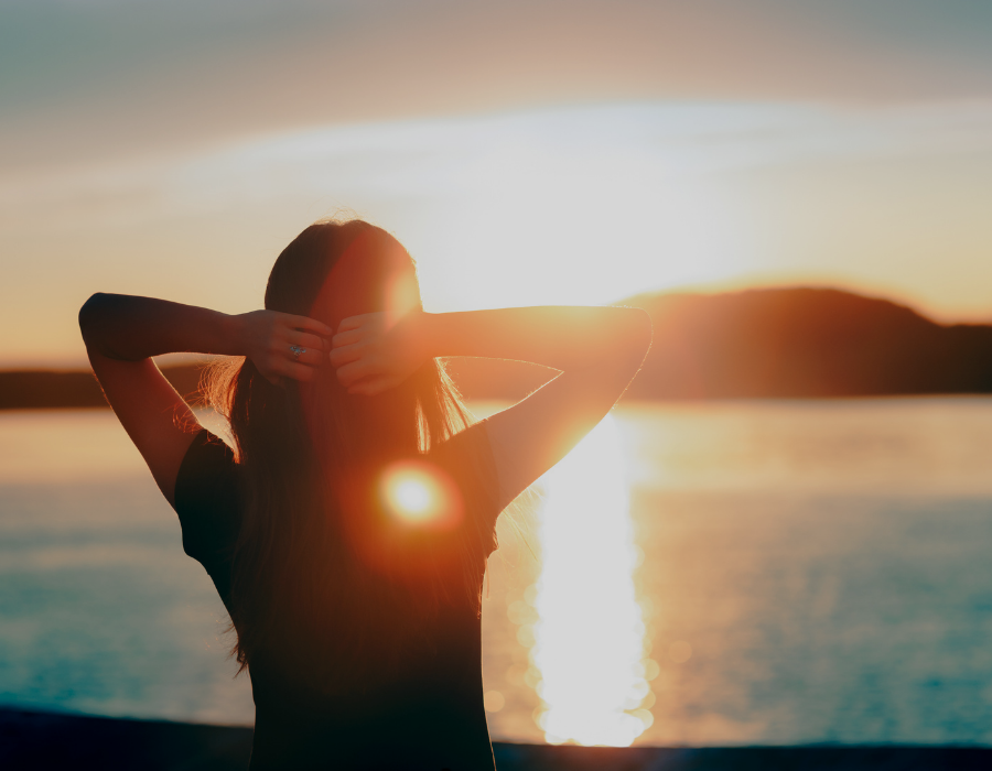 Lady looking into sunrise with hands behind head