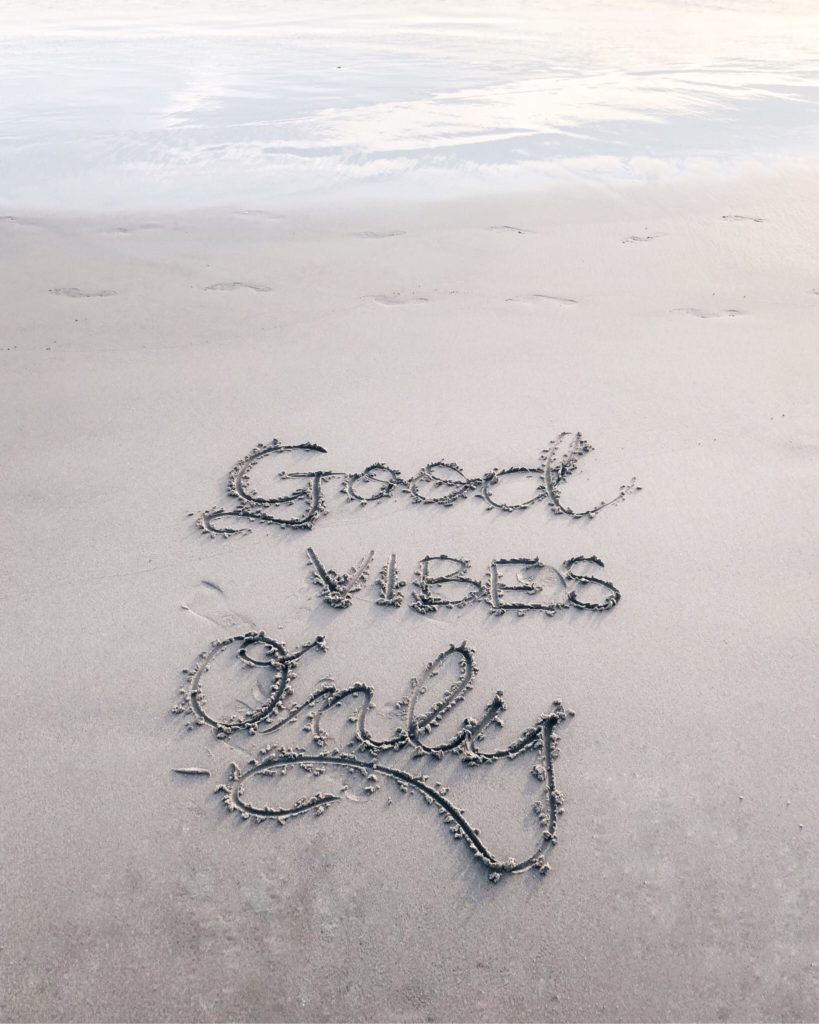 Good vibes only words in beach sand uncrossed
